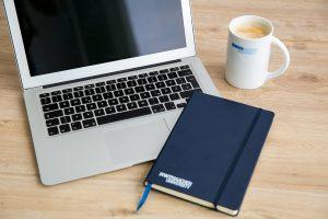 Laptop, Notizbuch und Kaffeetasse auf einem Tisch