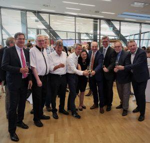 """Prof. Dr. Rüdiger, Rektor der RWTH Aachen University stößt mit Kolleginnen und Kollegen an, um den Erfolg der Titelverteidigung """"Exzellenzuniversität"""" zu feiern."""