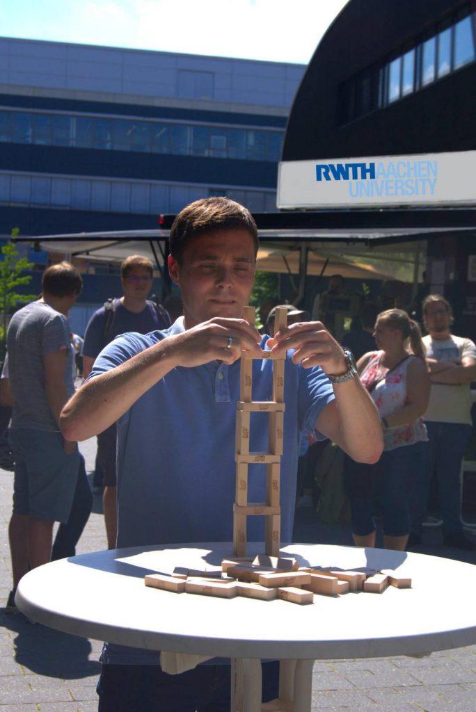 Herr Daniel Bündgens, Geschäftsführung IT Center, kreative Gestaltung mit Holzklötzen.