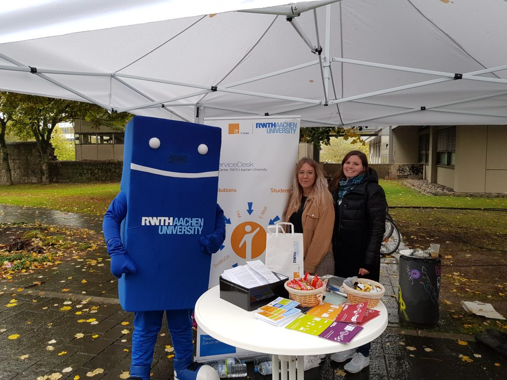 The IT Center booth at the Ersti Rally with the mascot of RWTH Aachen University and our employees Janina Claer and Linda Jörres (from left to right).