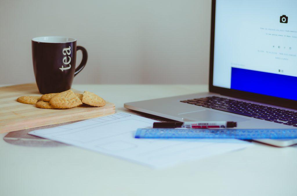 Laptop mit Teetasse und Keksen daneben.