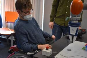Person im Rollstuhl an inklusivem Arbeitsplatz mit Roboter des NextGeneration-Projektes